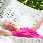 Senior Woman Relaxing In Beach Hammock